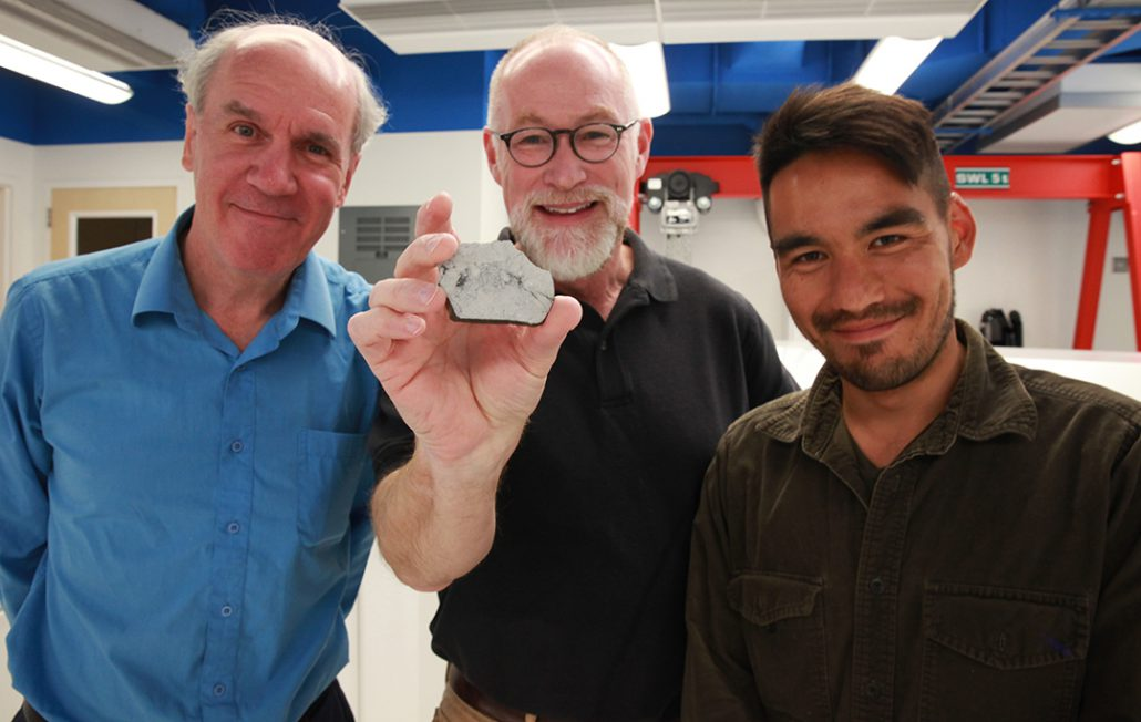Paul Warren, Edward Young and Issaku Kohl. Young is holding a sample of a rock from the moon.