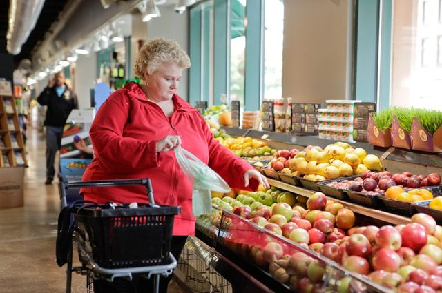 A woman shopping in the produce department of a grocery store.