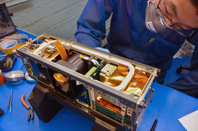 Photo of Ethan Tsai working on flight model assembly