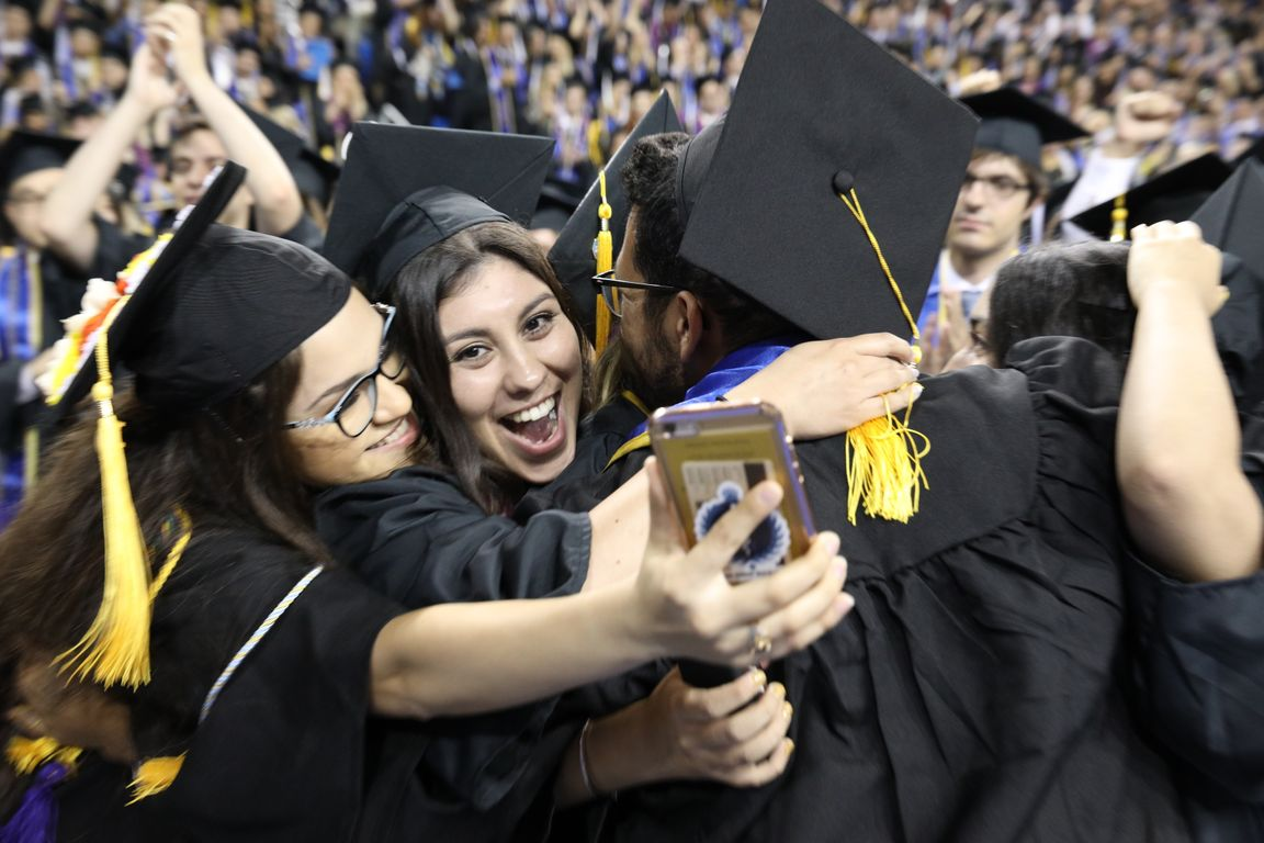 Graduates in Pauley Pavilion taking selfies
