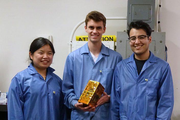 Bruin Space team members Chloe Liau, Andrew Evans, and Alexander Gonzalez holding their final flight model.
