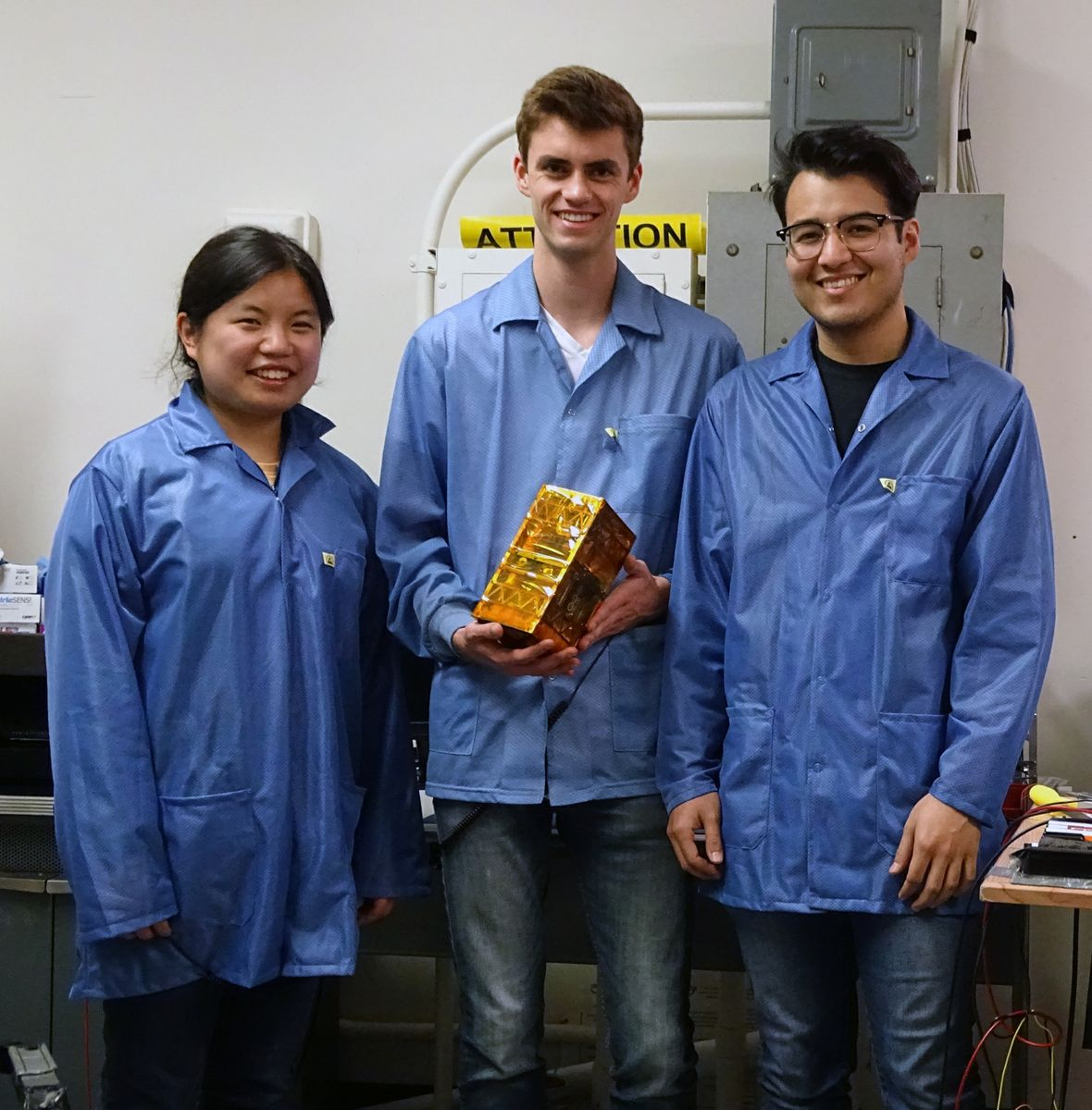 Bruin Space team members Chloe Liau, Andrew Evans, and Alexander Gonzalez holding their final flight model.