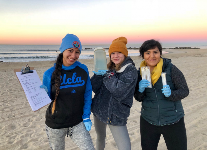 Student researchers on the beach hold up water samples for the camera