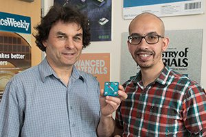 Photo of Richard Kaner, with Maher El-Kady, holding a replica of an energy storage and conversion device the pair developed.