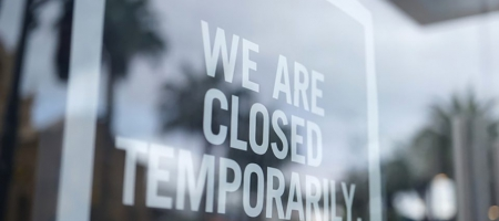 "A photo of a storefront with a sign that says ""We are closed temporarily."""