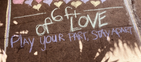 "A photo of the sidewalk with chalk that says ""Play your part, stay apart"""
