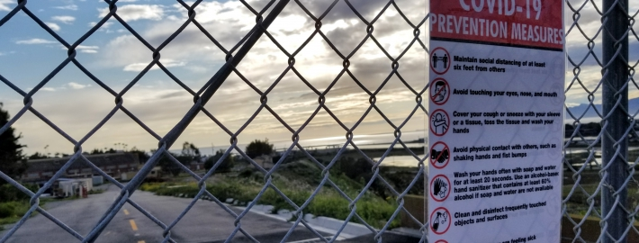 A photo of a Covid-19 fence sign.