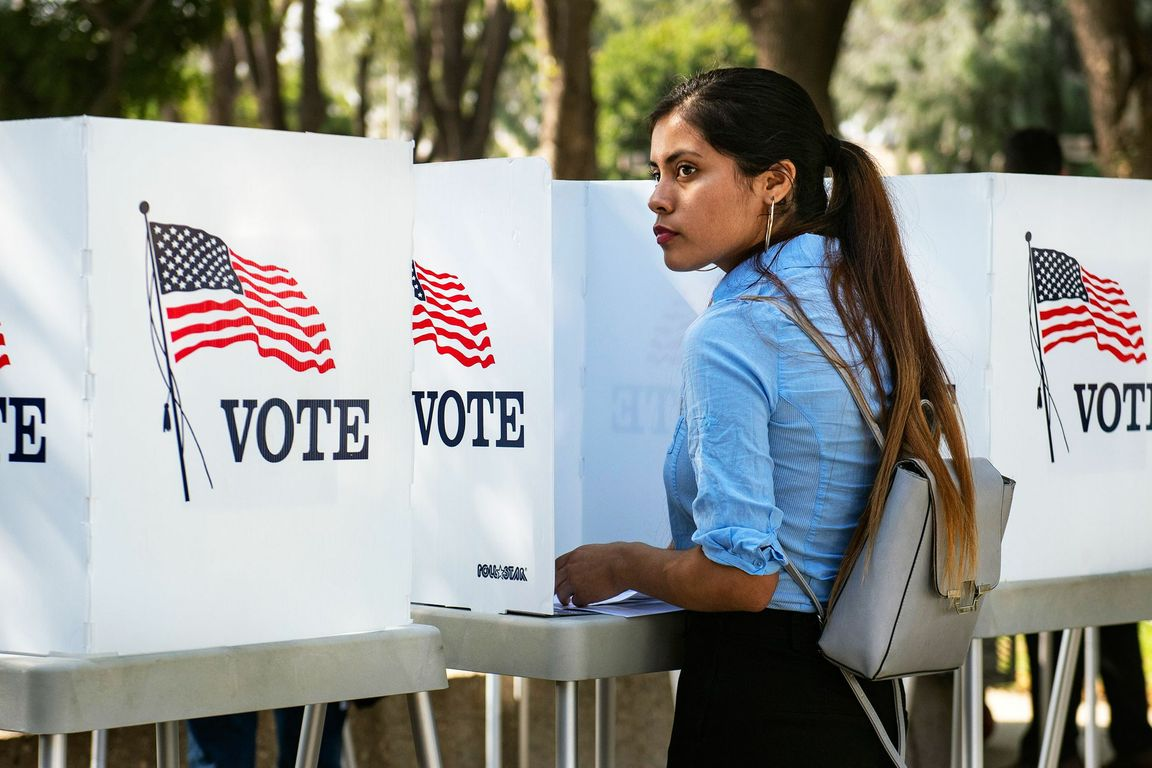 A photo of a woman at a voting booth.
