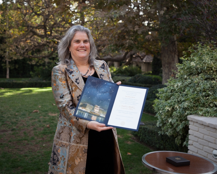 A photo of Andrea Ghez receiving her Nobel Prize citation and medal.