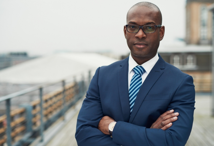 A photo of a Black man in suit and tie.
