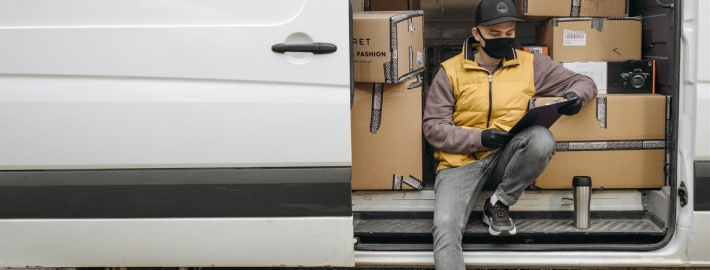 A photo of a worker wearing a face covering on a delivery truck.