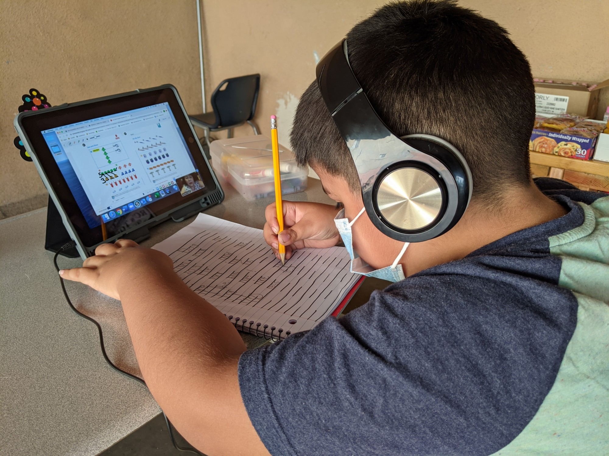Young boy with school workbook and tablet computer