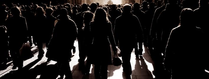 silhouetted people walking on busy street. iStock.com/imagedotpro