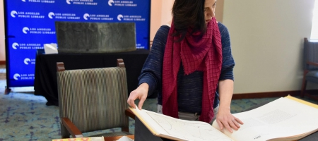 """Professor Marissa López examines Robert Becker's """"Diseños of California Ranchos: Maps of thirty-seven Land Grants if 1822-1846 from the Records of the United States District Court, San Francisco"""" in the Rare Books room at Central Library downtown. PHOTO CREDIT: Yvonne Condes"""